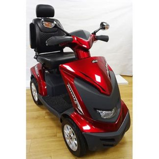Angled view of the red and black detailed scooter, showing the seating area with headrest, tyres, steering tiller and lighting system (indicators and headlight).